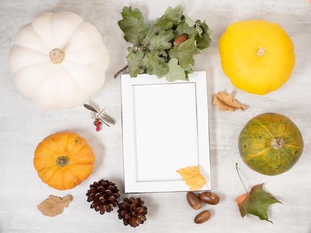 가 마른 나뭇잎과 장식용 호박에 빈 흰색 사진 프레임의 최고 볼 수 있습니다.