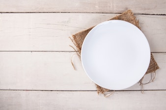 Top view of empty white plate put on sack and white wood table with space for copy.