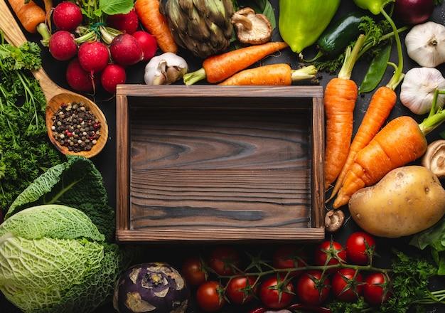 素朴な黒いコンクリートの背景に空の木箱と新鮮な農場の有機野菜の上面図。秋の収穫、ベジタリアン料理、またはテキスト用のスペースを備えた清潔で健康的な食事のコンセプト