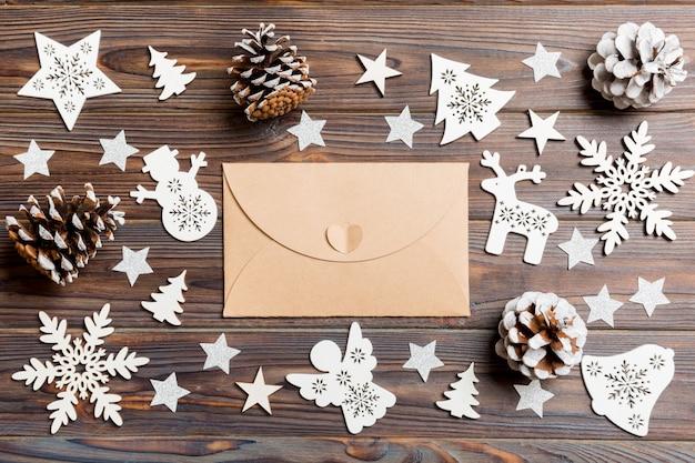 お祝い木製テーブルの上の封筒の平面図。クリスマスのおもちゃと装飾。新年の時間の概念