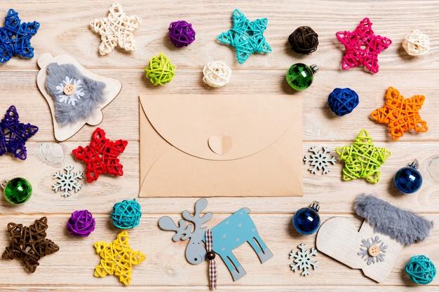 お祝い木製テーブルの上の封筒の平面図。クリスマスのおもちゃと装飾。