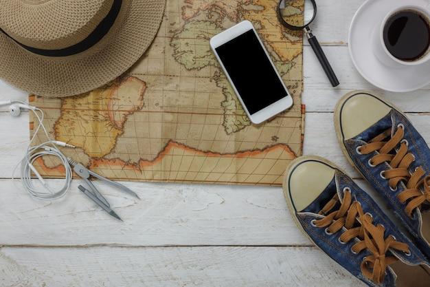 여행 및 기술 배경 개념에 대 한 필수 항목의 상위 뷰. 여행자를위한 여러 가지 액세서리와 함께 차 한잔 들고 손 남자의 오버 헤드 여행 및 휴가를 준비합니다. 현대 나무에 개체