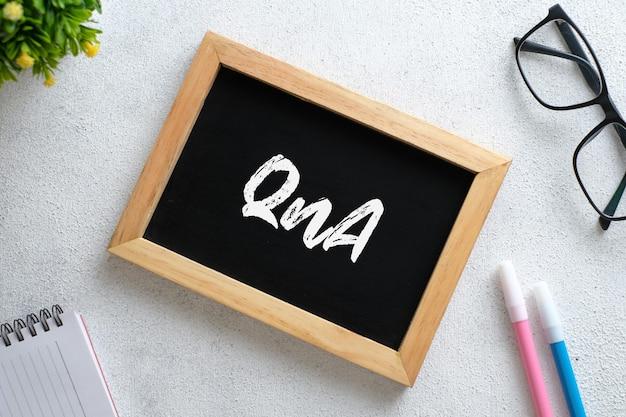 Взгляд сверху очков и деревянной доски написанный с текстом q и a над деревянным фоном. бизнес-концепция.