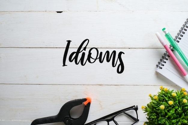 白い木製の背景の上に手書きの「イディオム」と眼鏡、植物、ペンの上面図。