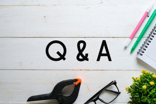 白い木製の背景の上にqn aを書いた眼鏡、植物、ペンの上面図。