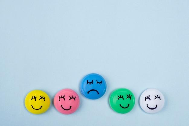 Вид сверху на лица с грустными и счастливыми эмоциями на синий понедельник с копией пространства