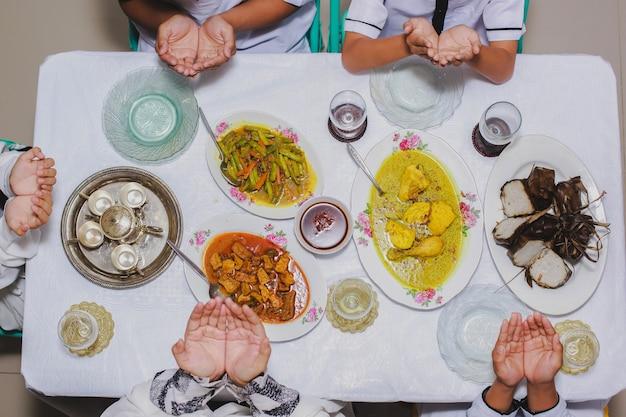 Вид сверху на семейные руки, молящиеся перед едой с меню, подаваемым на стол во время ид мубарак