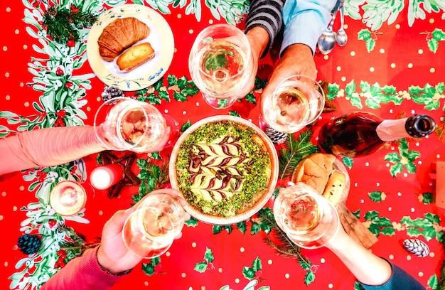 Вид сверху на руки семьи, поджаривающие бокал шампанского на вечеринке по случаю воссоединения рождественского дома