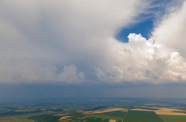농지와 극적인 구름의 최고 전망 극적인 하늘이 있는 아름다운 평원의 공중 전망