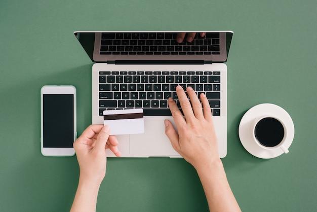 Вид сверху модного офисного стола с кредитной картой для онлайн-платежей на портативном компьютере