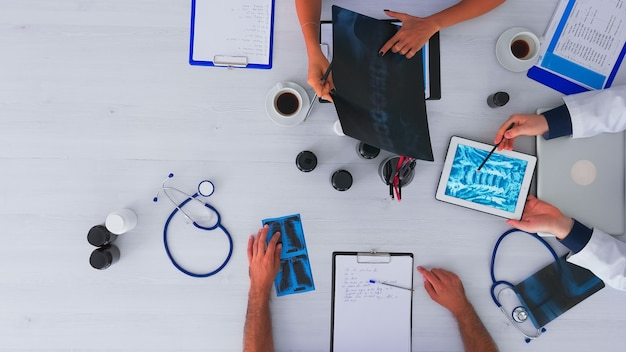 디지털 기술을 사용하여 책상에 앉아 의료 회의를 갖는 의사의 빨리 감기 샷, 메모 작성, 약속 조사 및 확인