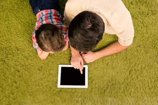 タブレットと緑のカーペットの上に横たわっている父と息子の平面図