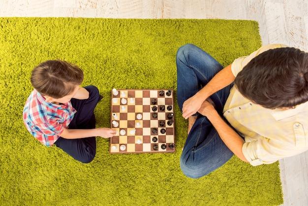 じゅうたんの上に座ってチェスをしている父と息子の上面図