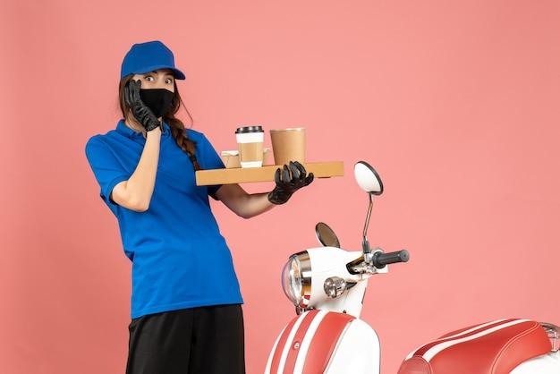 パステル ピーチ色の背景にコーヒーの小さなケーキを保持しているオートバイの隣に立っている医療マスク手袋を着た恐ろしい宅配便の女の子のトップ ビュー