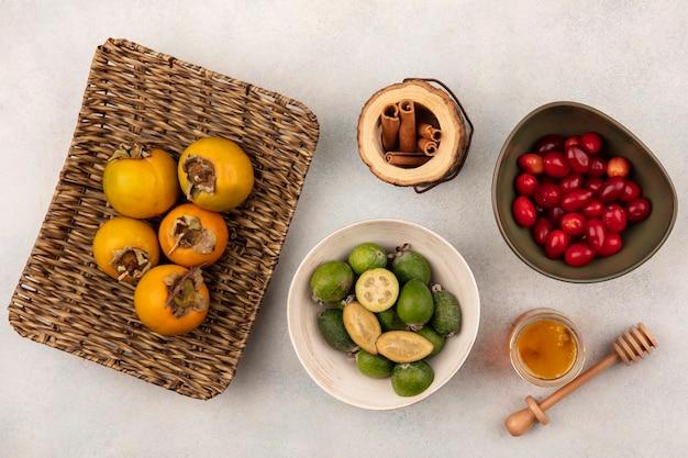灰色の表面のガラスの瓶に蜂蜜と蜂蜜とボウルにシナモンスティックとシナモンスティックと籐のトレイに柿とボウルのフェイジョアの上面図