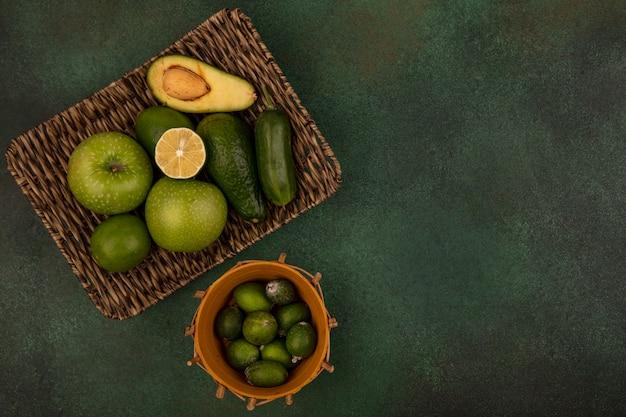 コピースペースのある緑の表面の枝編み細工品トレイに青リンゴアボカドキュウリとバケツのフェイジョアの上面図