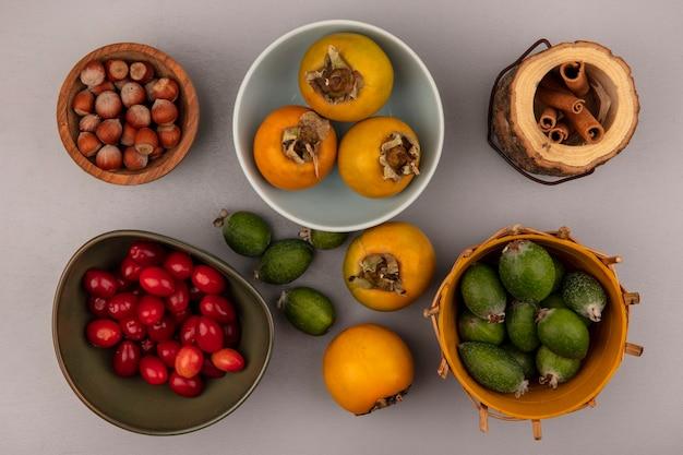 灰色の壁にシナモンスティックが付いた木製のボウルにヘーゼルナッツが入ったボウルにコーネリアンチェリーが入ったボウルに柿が入ったバケツのフェイジョアの上面図