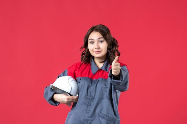 하드 모자를 들고 격리 된 빨간색 배경에 확인 제스처를 만드는 여성 건축가의 상위 뷰