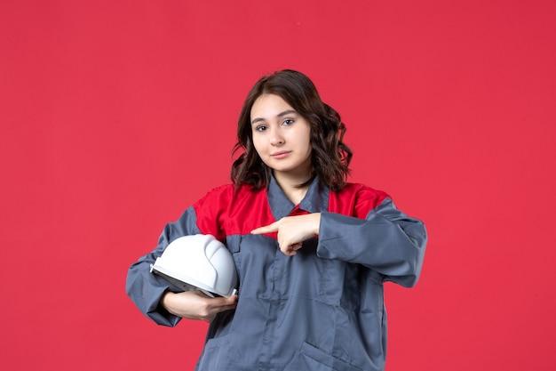 하드 모자를 들고 고립 된 빨간색 배경에 가리키는 여성 건축가의 상위 뷰