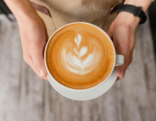 Вид сверху на женщину-бариста, держащую в руках украшенную чашку кофе