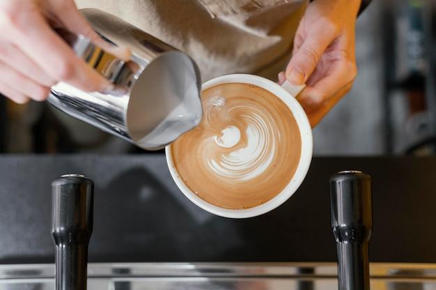 Вид сверху женщины-бариста, использующей молоко для украшения чашки кофе