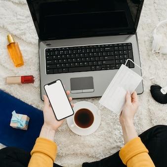 노트북과 스마트 폰으로 집에서 스트리밍하는 여성 블로거의 상위 뷰