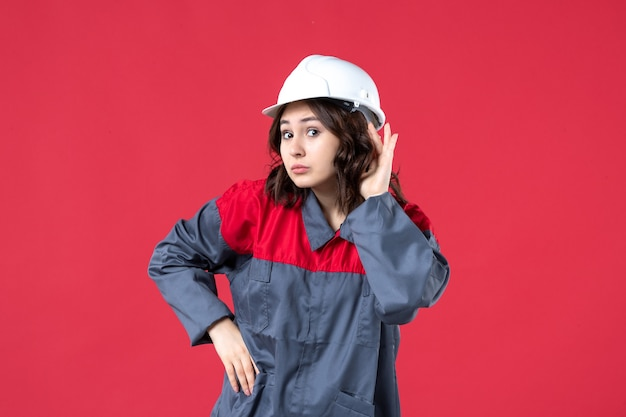 Вид сверху на женщину-строителя в униформе с каской и слушающую последние сплетни на изолированном красном фоне