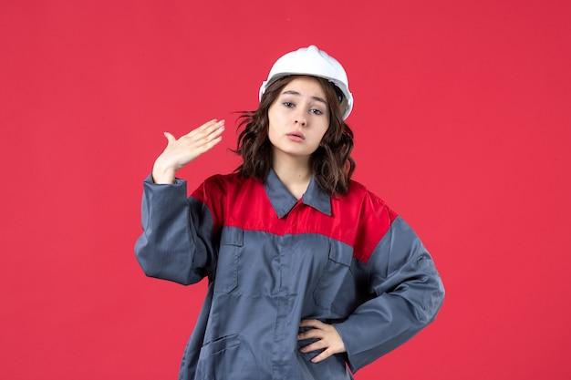 모자를 쓰고 고립된 빨간색 배경에 문제가 있는 제복을 입은 여성 건축업자의 상위 뷰
