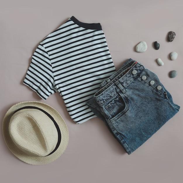 Вид сверху на женский повседневный модный летний наряд с джинсовыми шортами, полосатым топом и отпускной соломенной шляпой ...