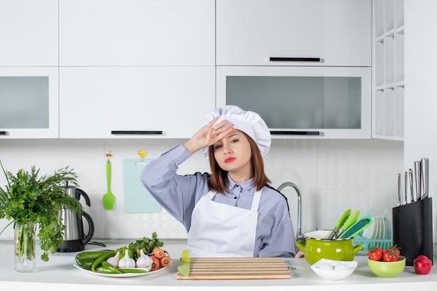 白いキッチンで頭痛に苦しんでいる女性シェフと新鮮な野菜の上面図