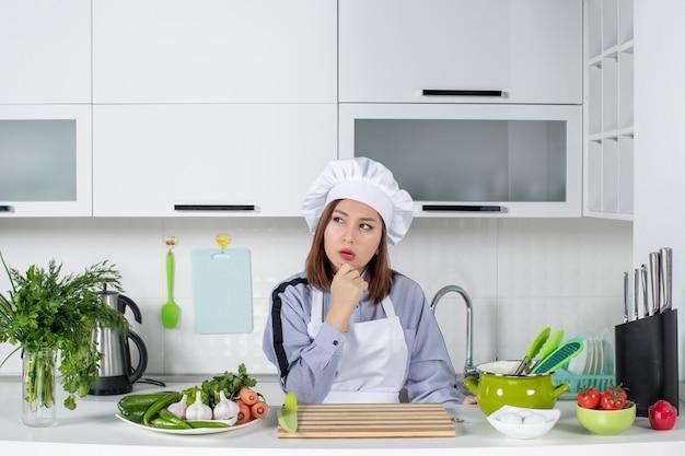 白いキッチンで深く考えている女性シェフと新鮮な野菜の上面図