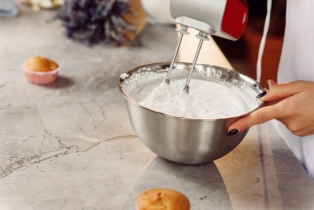 女性のお菓子の平面図は、焼きたてのカップケーキの赤いキッチンミキサーで深い金属板に白いクリームを混ぜます。