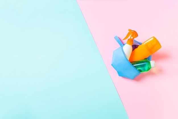 Вид сверху женской косметички, полной спрея для загара, солнцезащитного крема, солнцезащитного крема, лосьона для тела и крема spf на синем и розовом фоне с копией пространства. прямо вверху. яркое летнее понятие.