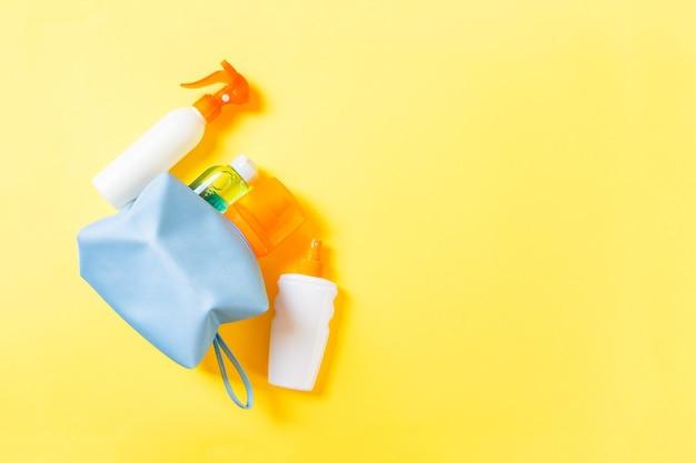 コピースペースと黄色の背景に日焼け止めスプレー、日焼け止め、日焼け止め、ボディローションとspfクリームでいっぱいの女性の化粧品バッグの上面図。真上。明るい夏のコンセプト。