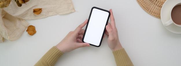Вид сверху женского фрилансера с помощью макета смартфона, чтобы связаться с клиентом на стол завтрак