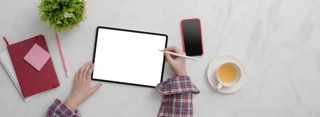 Взгляд сверху фрилансера женского пола работая на таблетке пустого экрана, smartphone, поставках и чашке чая