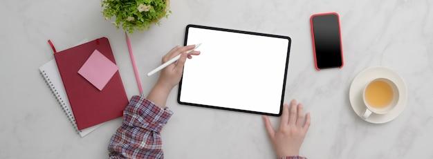 Вид сверху женского фрилансера, работающего с планшетом, смартфоном, расходными материалами и чашкой чая