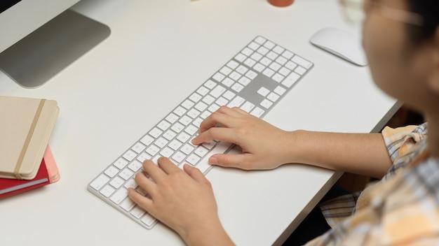 Вид сверху на женщину-фрилансера, работающую с компьютерным устройством в минималистичной офисной комнате