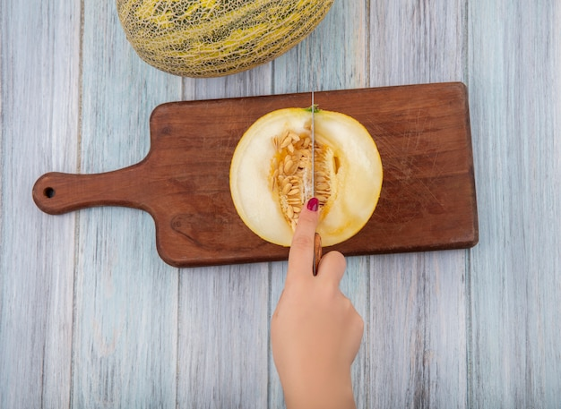 灰色の木の木製キッチンボード上のナイフで女性の手切断メロンのトップビュー