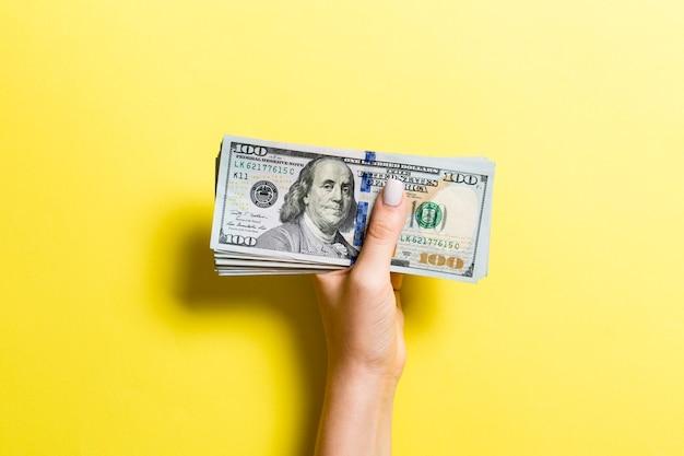 Вид сверху женской руки, давая сто долларовых купюр на красочном фоне. концепция благотворительности и пожертвований.