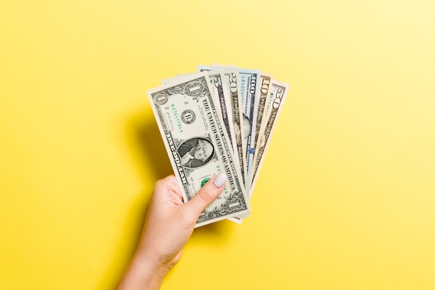 Вид сверху женской руки, давая различные долларовые купюры на красочном фоне. концепция благотворительности и пожертвований.