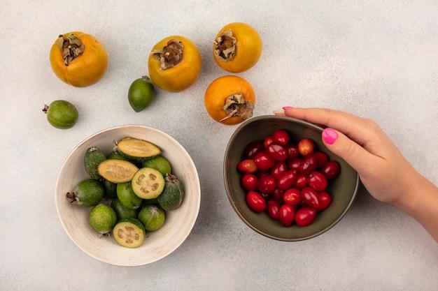 ボウルにフェイジョアと灰色の表面に分離された柿とコーネリアチェリーのボウルを持っている女性の手の上面図