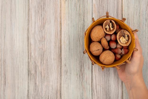 コピースペースのある灰色の木の表面にクルミやヘーゼルナッツなどのさまざまなナッツのバケツを持っている女性の手の上面図