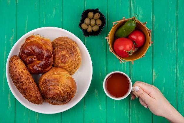 緑の背景の上のバケツにトマトとキュウリとトマトとキュウリの黒いボウルにオリーブとオリーブと白いプレートにパンとお茶のカップを持っている女性の手の上面図