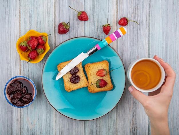 灰色の木製の背景に新鮮なイチゴといちごジャムとお茶のカップを持っている女性の手の上から見る