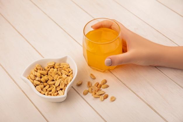 Вид сверху женской руки, держащей стакан апельсинового сока с кедровыми орехами в миске на бежевом деревянном столе