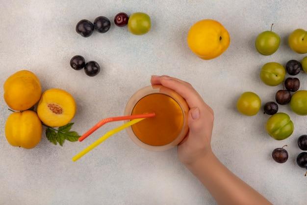 白い背景に分離された緑のチェリープラムと新鮮な桃と桃ジュースのガラスを持っている女性の手の上から見る