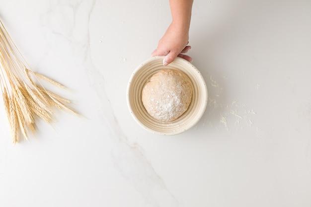 텍스트에 대 한 공간을 가진 밀가루와 밀가루 대리석 테이블에 빵 그릇에 휴식 빵 반죽을 들고 여성 손의 상위 뷰