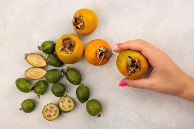灰色の表面に分離されたフェイジョアと柿と有機柿の果実を持っている女性の手の上面図