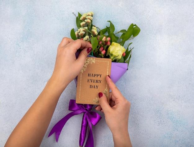 白の葉とピンクの果実とバラの花束を持っている女性の手の上から見る